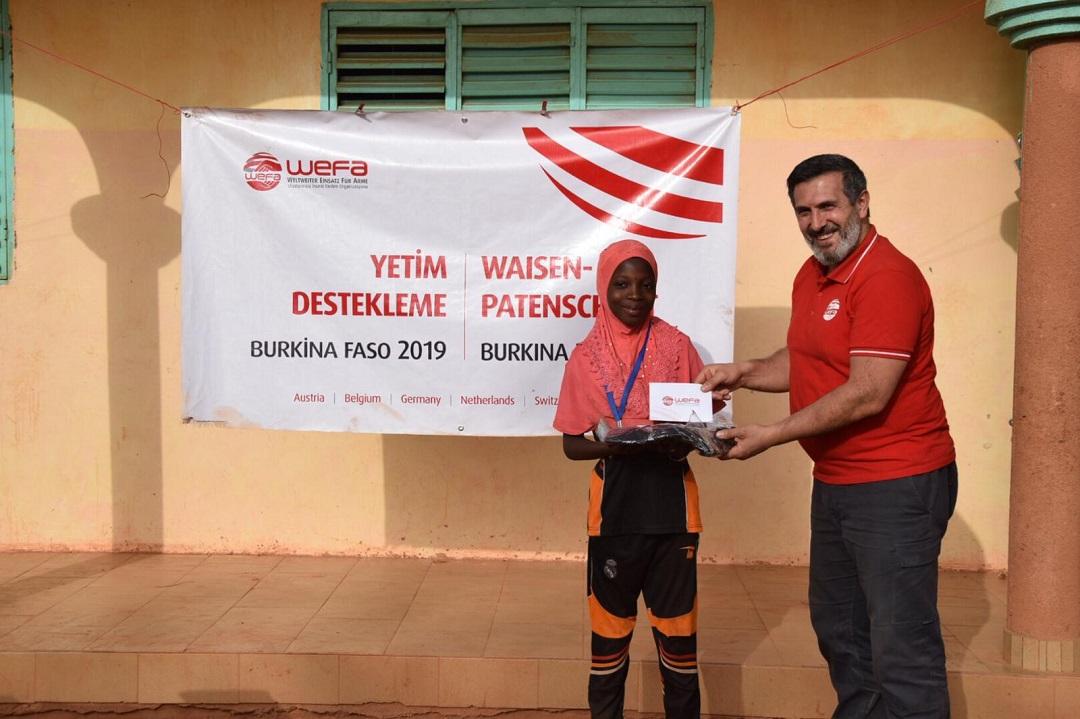 Burkina Faso'da hamiliğini üstlendiği yetimleri ziyaret eden WEFA Uluslararası İnsani Yardım Organizasyonu yetimlere harçlıklarını elden teslim etti.