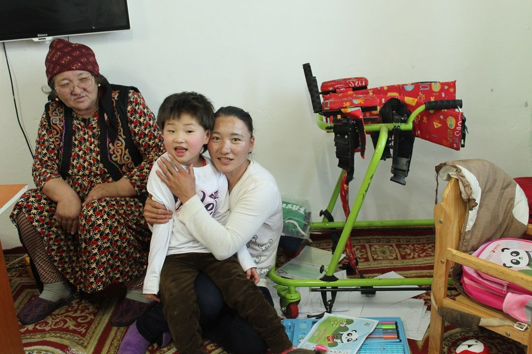 """Doğuştan engelli Nazım 6 yaşında. WEFA Uluslararası İnsani Yardım Organizasyonu """"Yetim Sponsorluğu"""" sistemiyle 2017 yılından beri Moğolistan'da yaşayan Nazım'ın hamiliğini üstlenmekte ve Nazım'a düzenli olarak destek vermektedir. Doğum günü vesilesiyle evinde ziyaret ettiğimiz Nazım'a keyifle oynaması için bir boyama kitabı hediyoruz ve o ise büyük bir heyecan ile bize alkış tutarak teşekkür ediyordu. Bu masum yavruyu daha yakından tanımak ve sizlere tanıtmak için 3 Aralık Dünya Engelliler Günü münasebetiyle Nazım'ın annesi Amangül Bergen ile kısa bir söyleşi gerçekleştirdik."""